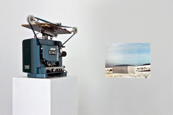 Ein EIKI Projektor projiziert ein beinahe sepia farbenes Bild eines sich ausdehneden Wellblechhauses auf eine weiße Wand.